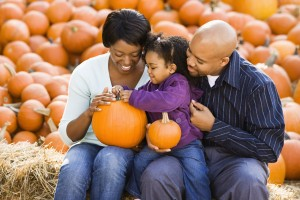 Happy family sitting on hay bales and holding pumpkins.